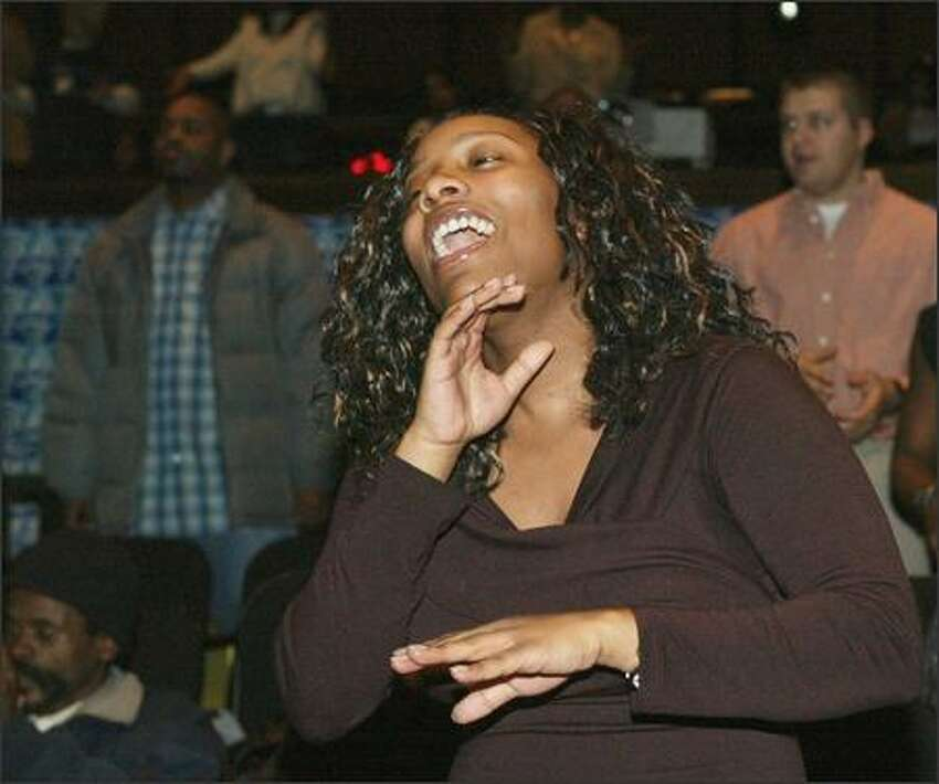 Jerrice Garrett, 21, of Seattle sings with the congregation at the Seattle International Church, which bustled as it gave away thousands of Toys for Tots.