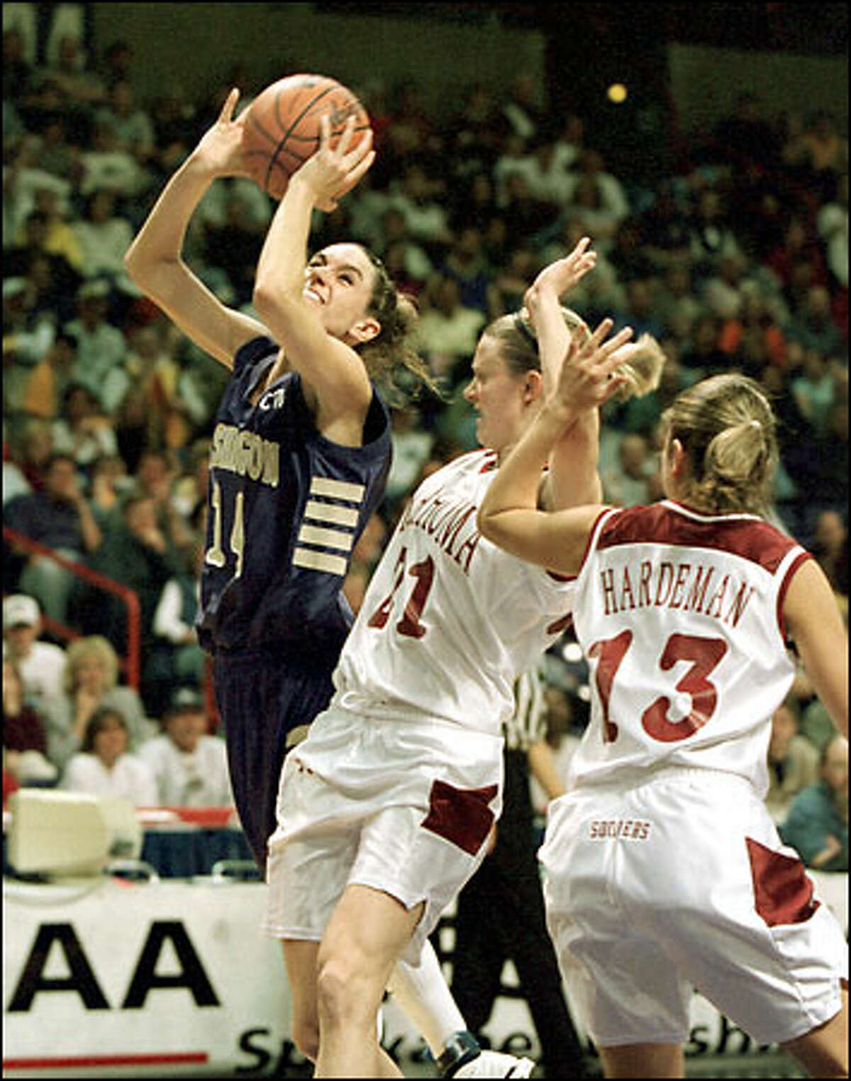 Washington's Megan Franza, left, works the ball to the basket against Oklahoma's Stacey Dales, center, and Sunny Hardeman during the second half. Franza finished with 17 points.