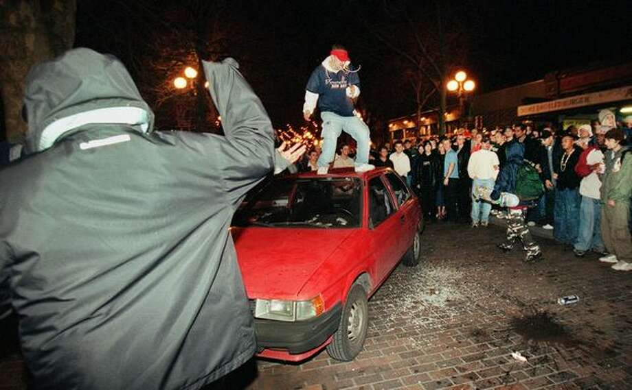 While a large crowd wateches, a man jumps on a car that was seriously damaged when Mardi Gras festivities in Pioneer Square turned ugly. Photo: Dan DeLong, Seattle Post-Intelligencer