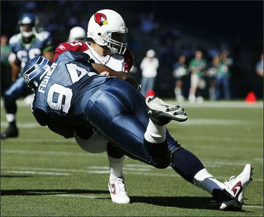 Seahawks' Bryce Fisher sacks Arizona Cardinals quarterback Kurt Warner for a loss of nine yards during second quarter action on September 25, 2005.