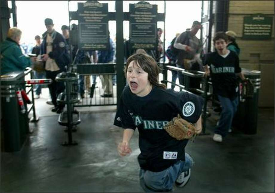Sam Bright, 11, from Oregon became the first fan in Safeco Field, working out a deal with a gate official who scanned his ticket a few seconds before the official opening. Photo: Joshua Trujillo, Seattlepi.com