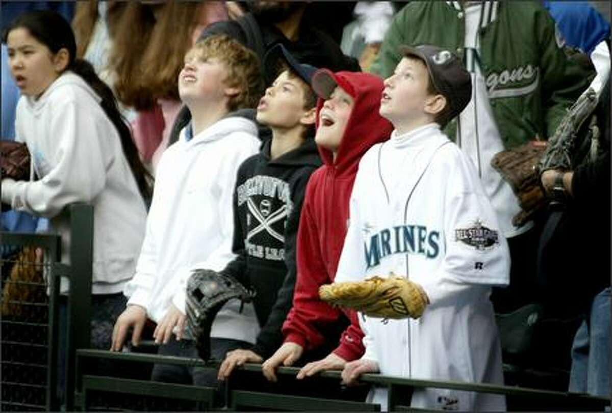 Young Mariners fans watch a ball hit toward them in right field during batting practice on Opening Day.