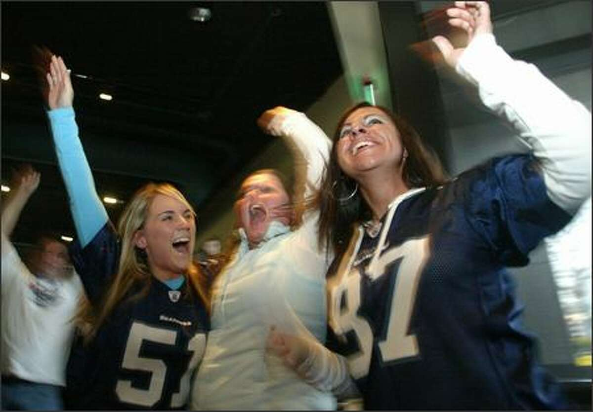 Seahawks fans, from left, Joanna Vogel, Theresa Miller and Hope Law celebrate during first-half action as they watch the Super Bowl at Sport Restaurant and Bar in Fisher Plaza.