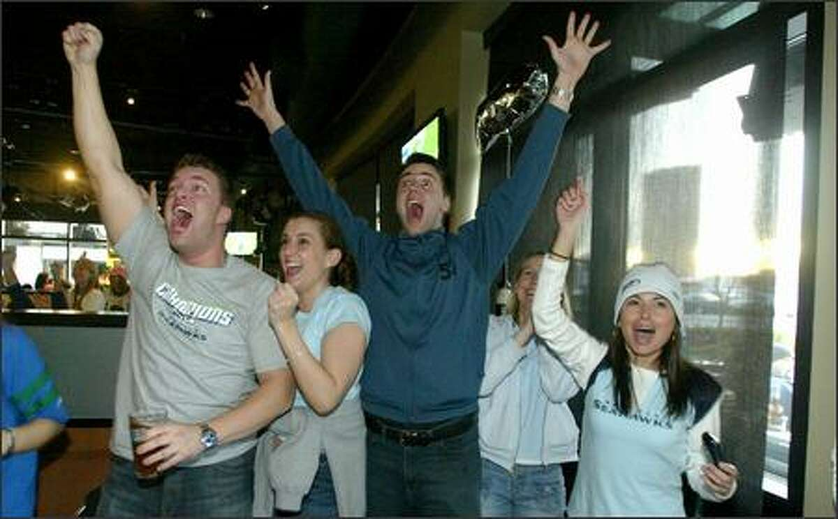 Seahawks fans, from left, Jon Wilmonth, Alicia Scalzo, Steve Francis, Vicky Francis, and Dangle Moore celebrate during first-half action as they watch the Super Bowl at Sport Restaurant and Bar in Fisher Plaza.