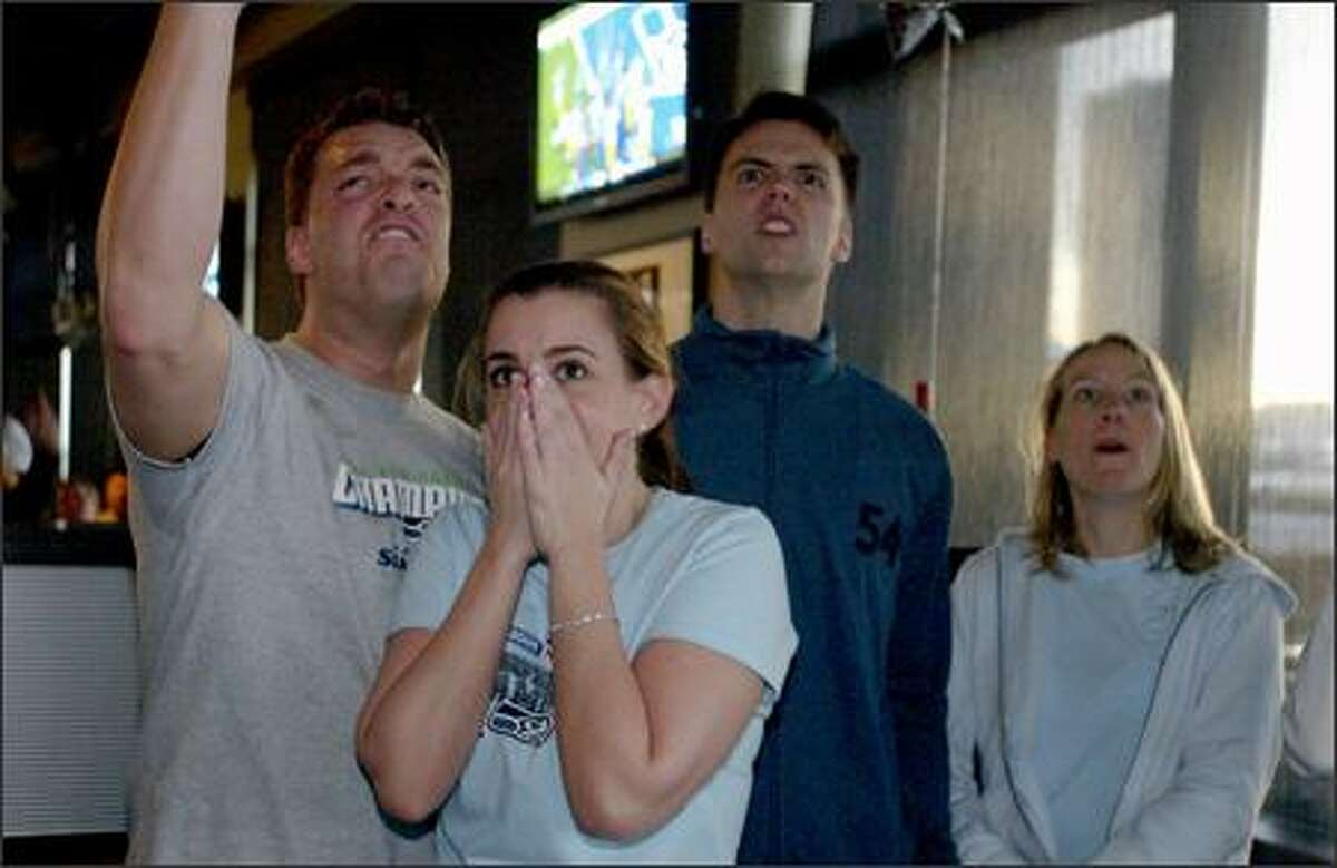 Seahawks fans, from left, Jon Wilmonth, Alicia Scalzo, Steve Francis and Vicky Francis celebrate during first-half action as they watch the Super Bowl at Sport Restaurant and Bar in Fisher Plaza.