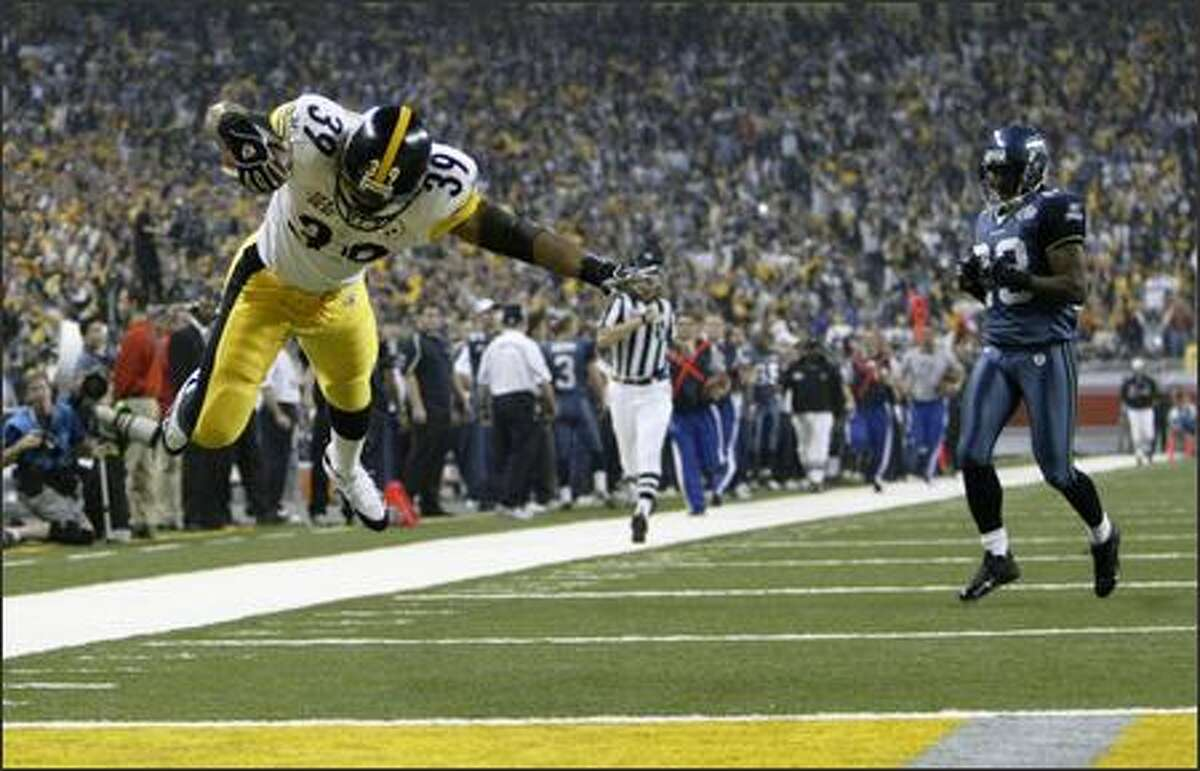 The Steelers' Willie Parker dives into the end zone after a 75-yard touchdown run, a Super Bowl record, as Marcus Trufant trails.