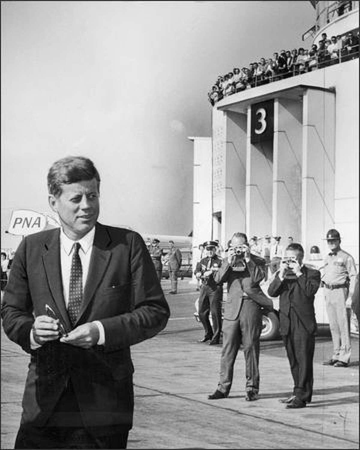 On September 27, 1963, President John F. Kennedy stands at Sea-Tac Airport as a crowd watches from the observation deck. Kennedy was assassinated less than two months later.