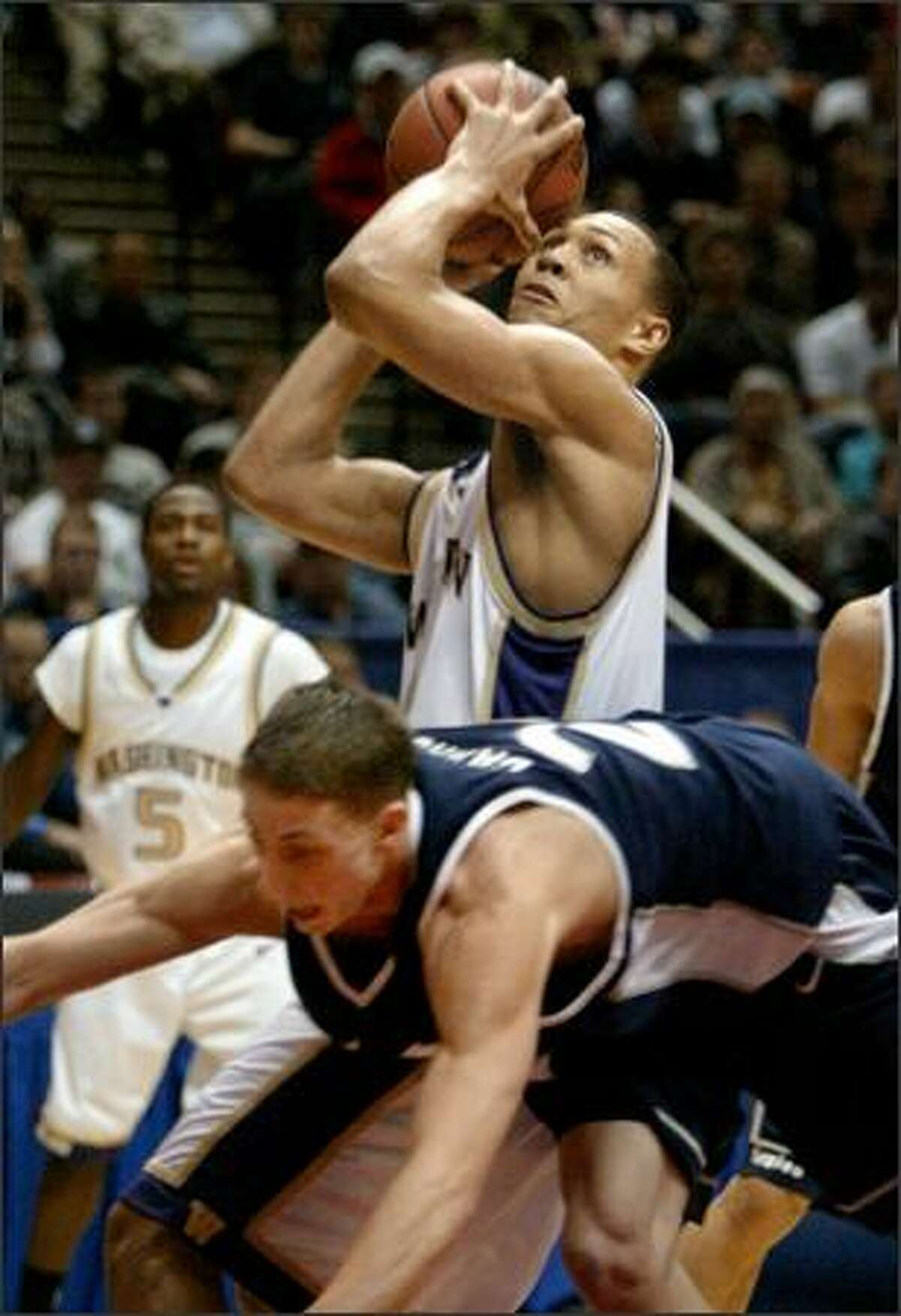 Utah State's Jaycee Carroll stumbles trying to keep up as Brandon Roy scores two of his game-high 28 points in the first half.
