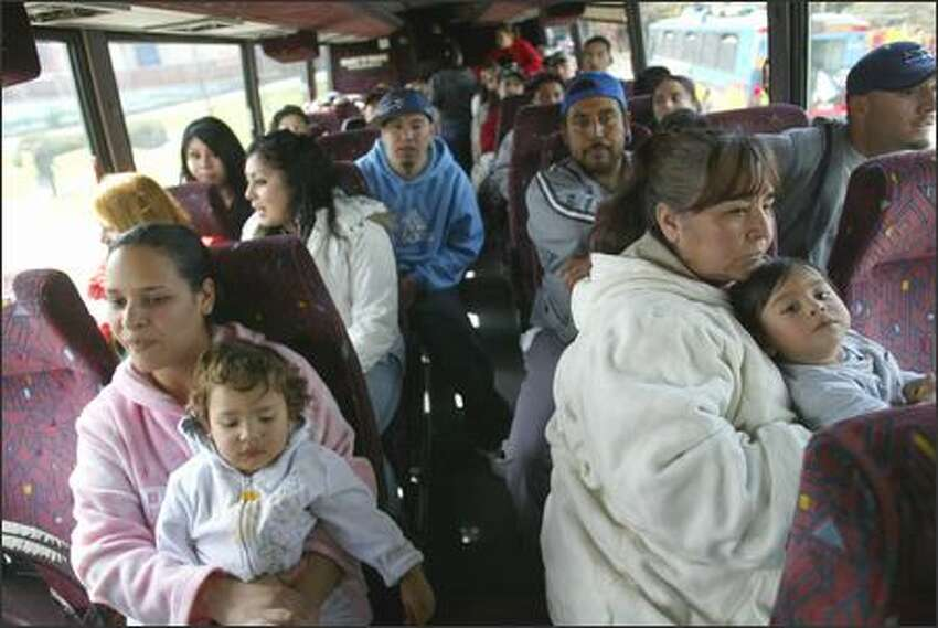 Rosario Cisneros, left, holding Jasmin Olmedo, 1, and Adela Lopez holding Jovani Lopez, 1, arrive with a busload of immigrants from Mount Vernon. More than 25,000 immigrants and their supporters rallied in Seattle on Monday during a national day of action in response to congressional action to punish illegal immigrants and those who help them. Many of the immigrants came from across the state to attend the rally.