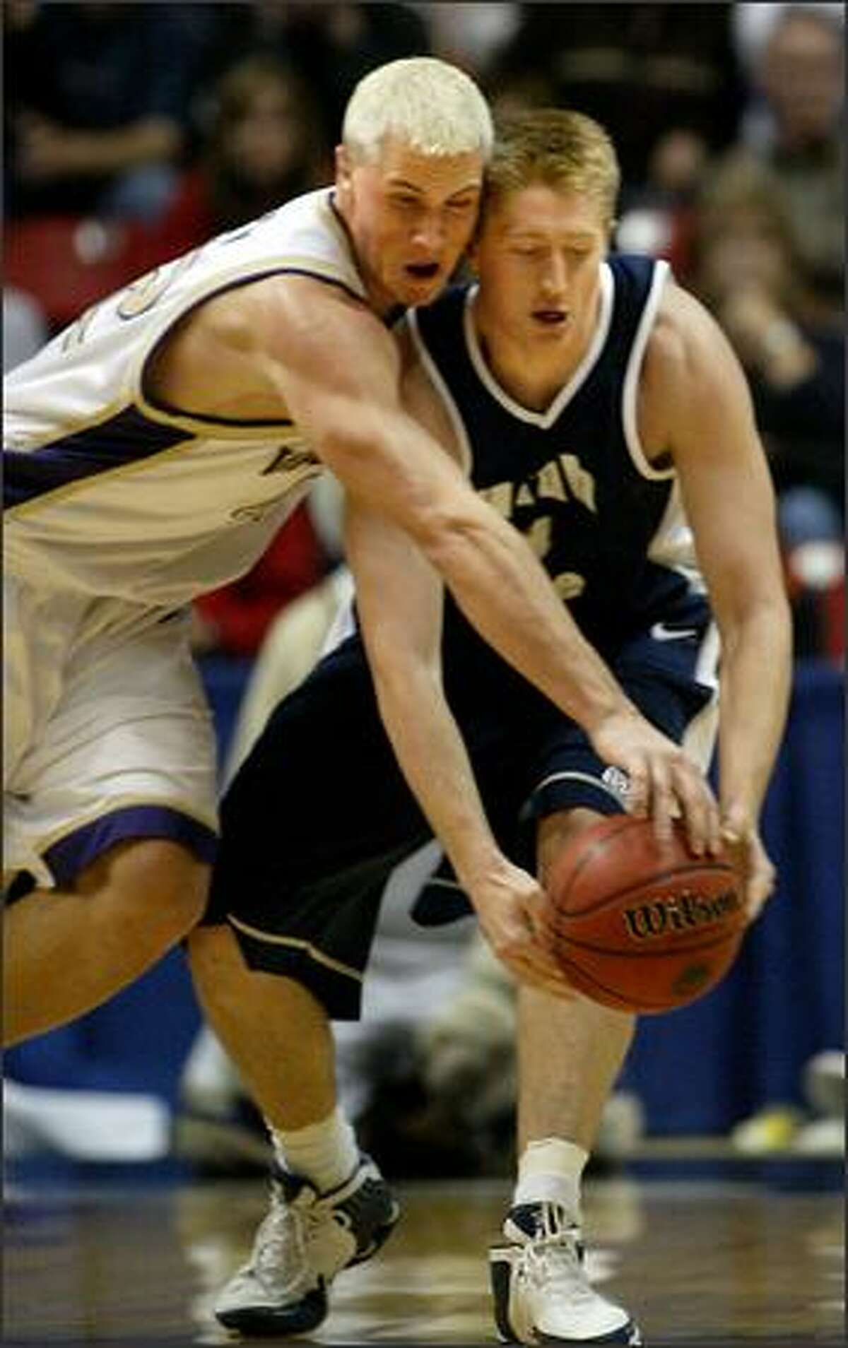 UW forward Mike Jensen (left) applies pressure on Utah State's Nate Harris while going after the ball.