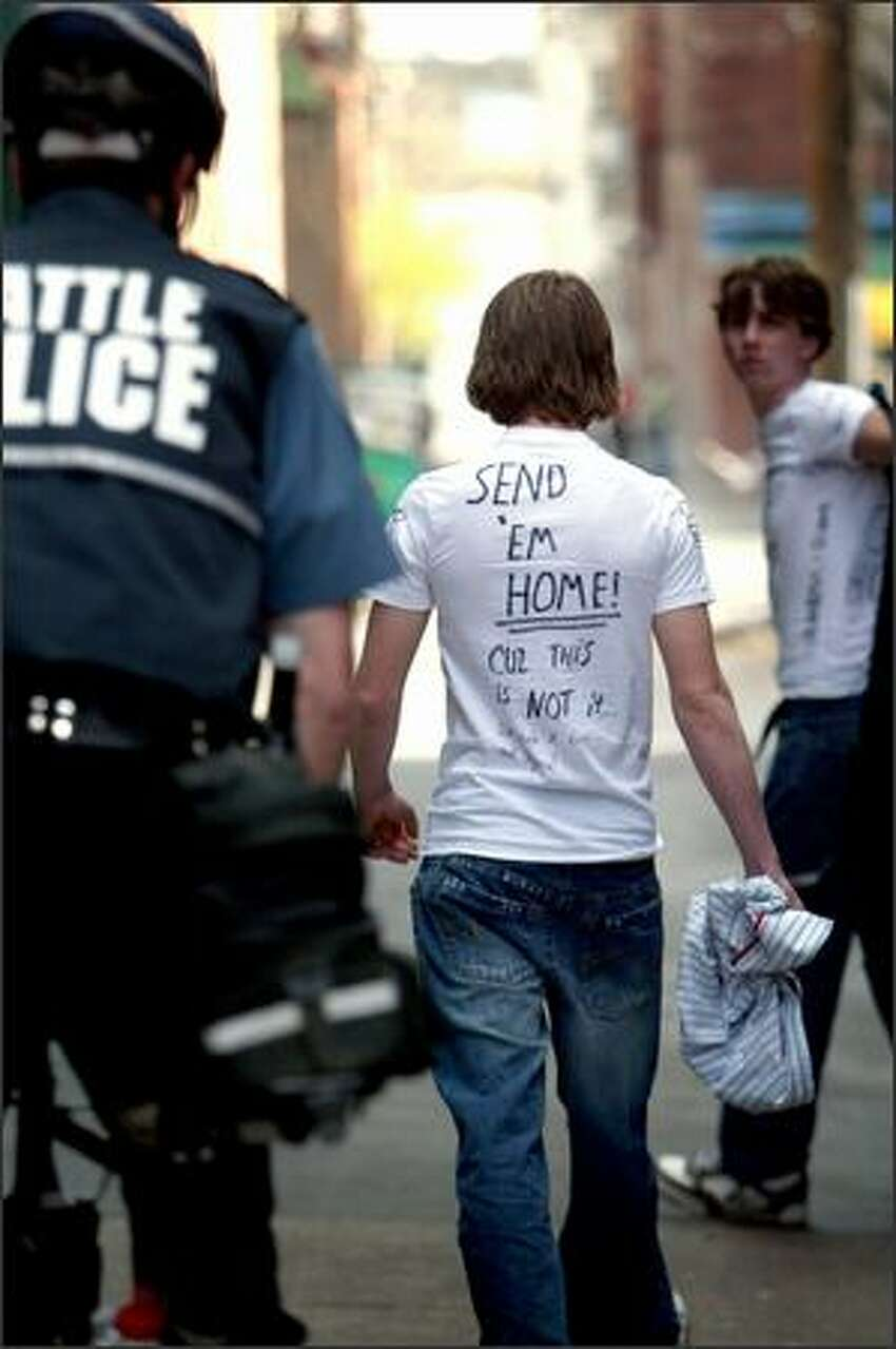 A self described white supremacist is escorted away after attempting to intercept the protest. The back of his T-shirt reads
