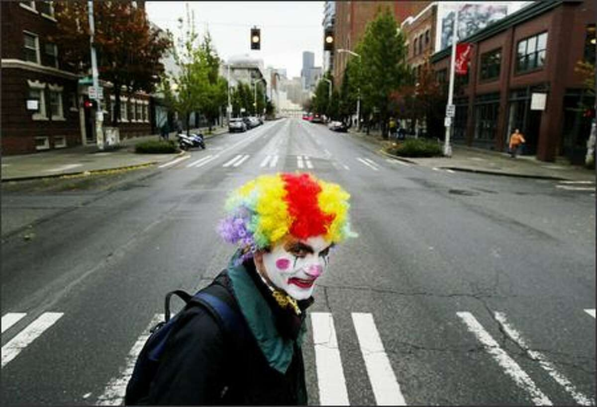 Sporting a clown face for Halloween, Larry Hohm, 49, of Seattle adds color to a gray Monday morning as he crosses Second Avenue on his way to work at Dwango Wireless.