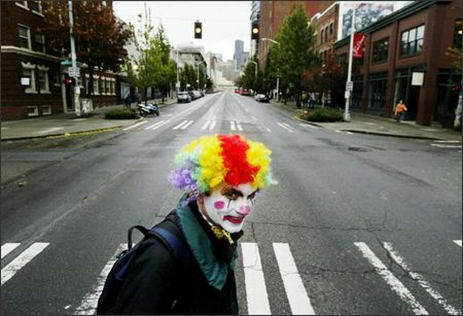 Sporting a clown face for Halloween, Larry Hohm, 49, of Seattle adds color to a gray Monday morning as he crosses Second Avenue on his way to work at Dwango Wireless. Photo: Dan DeLong, Seattle Post-Intelligencer
