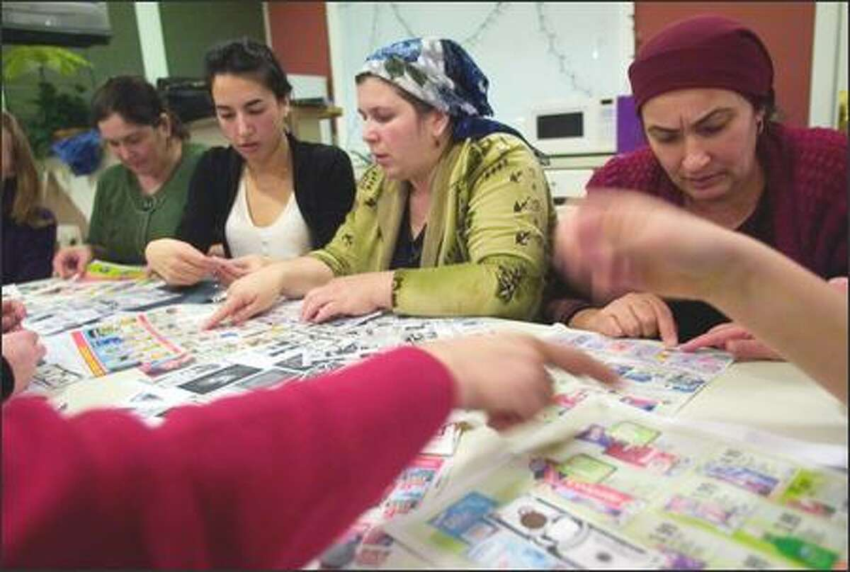 Meskhetian Turkish women Zumrud Gulaliyeva, left, Zamira Gulaliyeva, third from left, and Fatima Chakholova, right, try to learn the value of U.S. currency and how to use grocery store coupons. The instructor is Yasmine Tarhouni of IRC, second from left. The class was held Feb. 28, 2006, in the community room at The Samarra Apartments in Tukwila. Meskhetian Turk refugees are one of the newest refugee groups in the U.S. They have been here for less than one year. Most have relocated to the Seattle area.