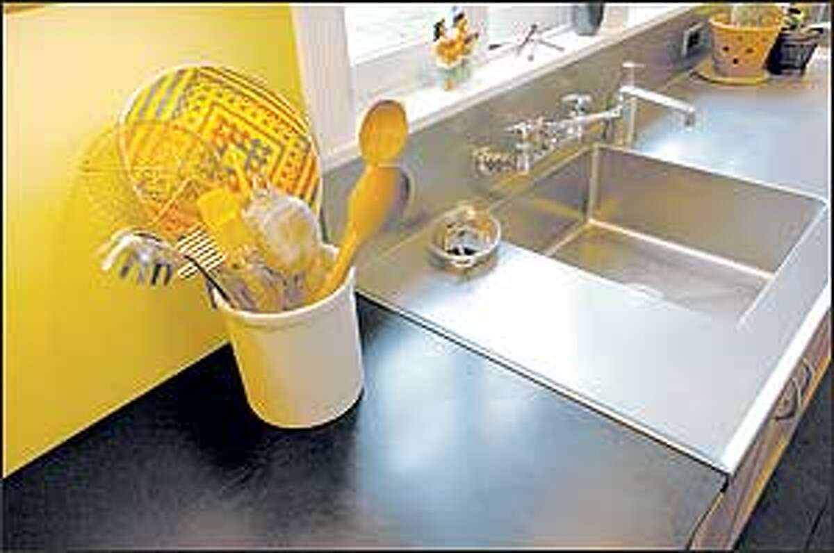 A Richlite countertop offers a sharp contrast to a stainless steel sink. Richlite, which is manufactured in Washington, is one of several eco-friendly countertop materials on the market.