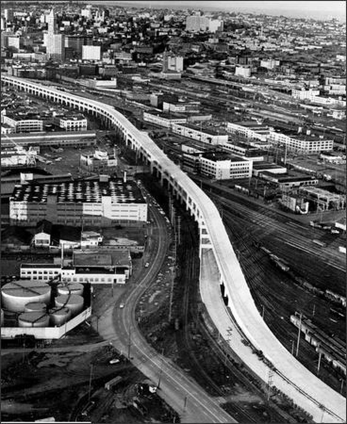 The southern portion of the Alaskan Way Viaduct was completed in late 1958. This photo, taken before cars were allowed on the span, looks northeast with Smith Tower at upper left.