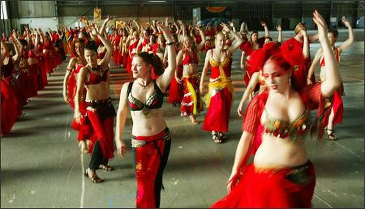 More than 100 belly dancers, including Kendra Schmidt, center left, and Laurarose Flynn, right, practiced Thursday at Hangar 27 in Magnuson Park for their Billion Belly March Saturday in the Fremont Solstice Parade.