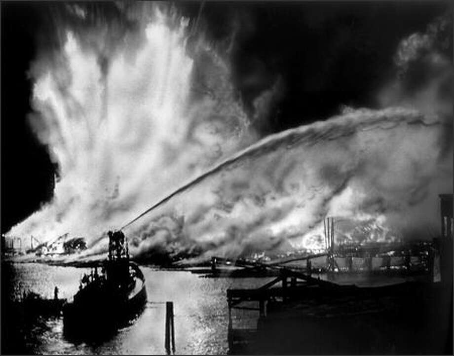 This view from the Ballard Bridge shows flame and smoke streaming from the Seattle Cedar Lumber Manufacturing Co. plant on the night of May 20, 1958. A fireboat pours water onto the fire, which leaps hundreds of feet into the air from the kiln and storage areas. Damage from the blaze was estimated at $1.5 million. Heat from the king-size blaze was felt more than two city blocks away. Photo: Phil H. Webber, Seattle Post-Intelligencer