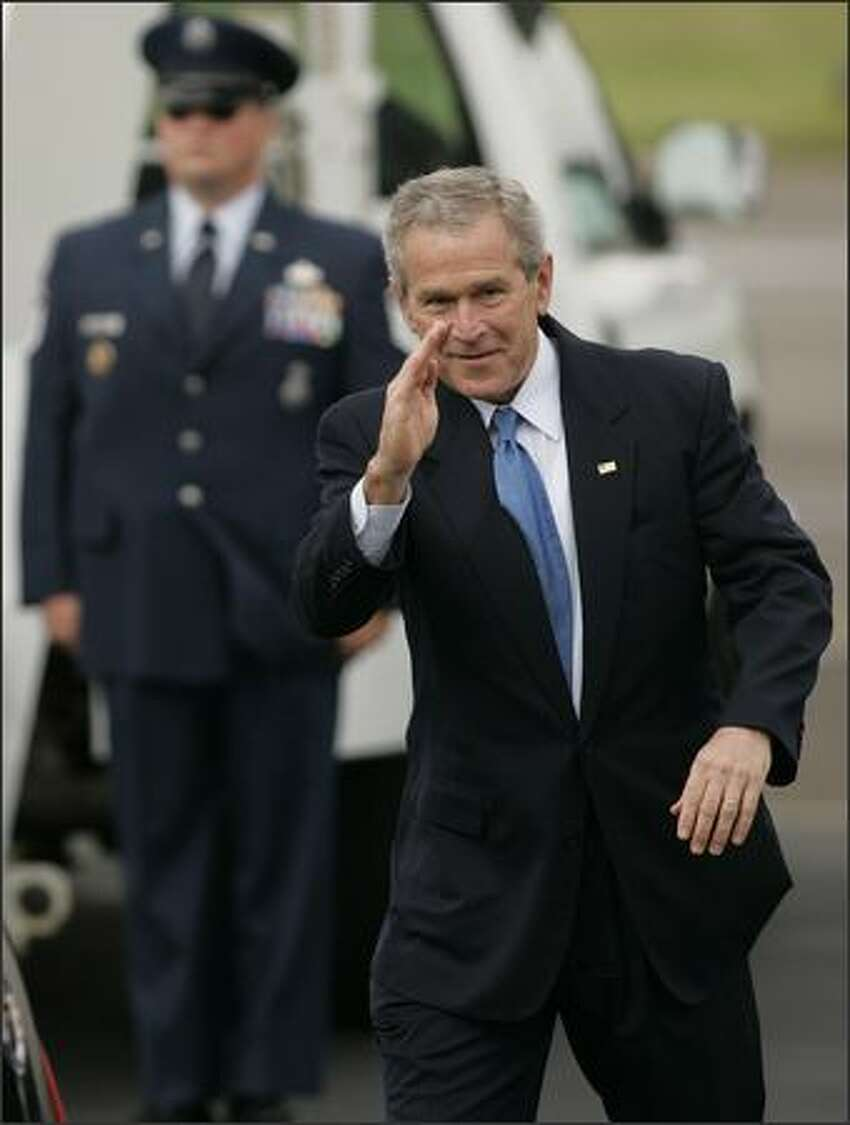 President George W. Bush salutes onlookers as he walks toward his awaiting limo after arriving at Boeing Field aboard Air Force One.