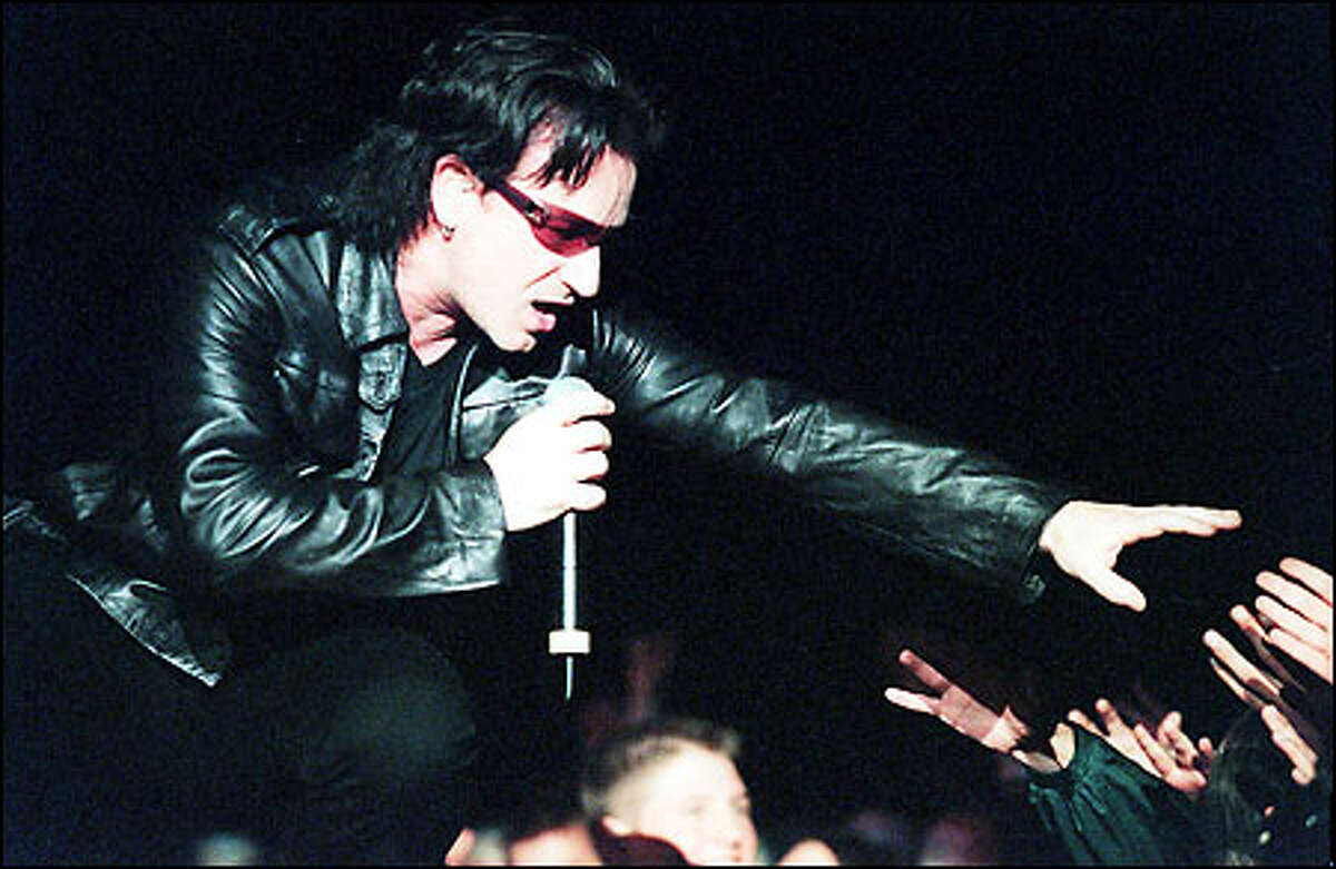 U2's lead singer Bono reaches out to the crowd pressing toward him on the catwalk stage during the