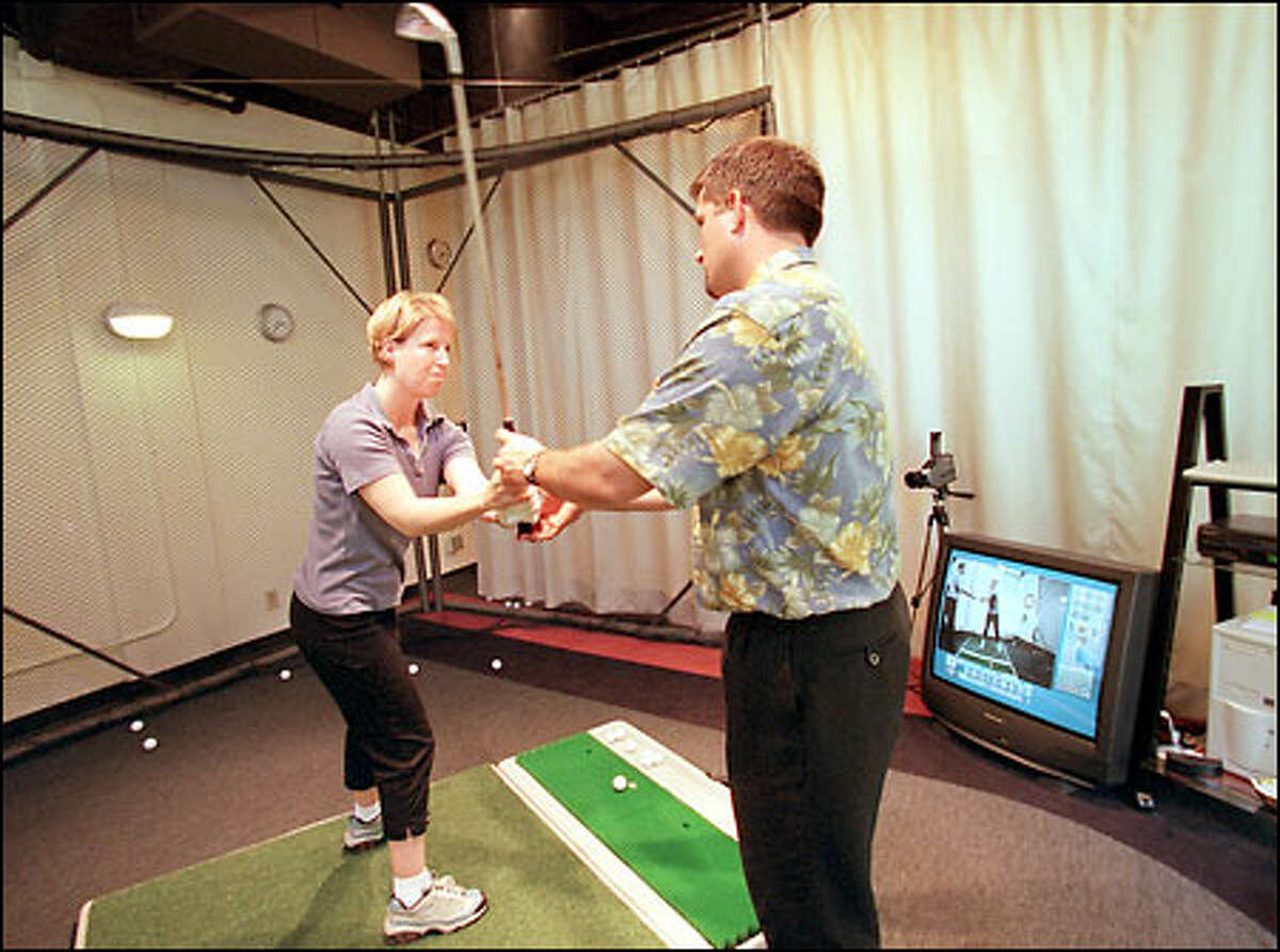 Lisa Beckman of Seattle receives a lesson from Bogart Golf teaching professional Dennis Stone.