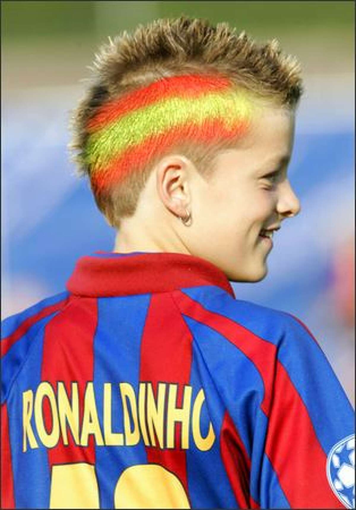 A girl wearing an FC Barcelona Ronalidnho jersey and with a Spanish flag painted in her hair is seen at a training session for Spain's national team. Spain will start the World Cup in Germany in group H with Ukraine, Tunisia and Saudi Arabia. (AP Photo/Bernat Armangue)