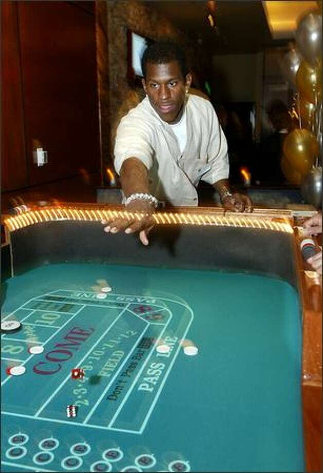 Seahawks safety Ken Hamlin tries his hand at the craps table while helping to raise funds and awareness for community programs. Photo: Scott Eklund, Seattle Post-Intelligencer