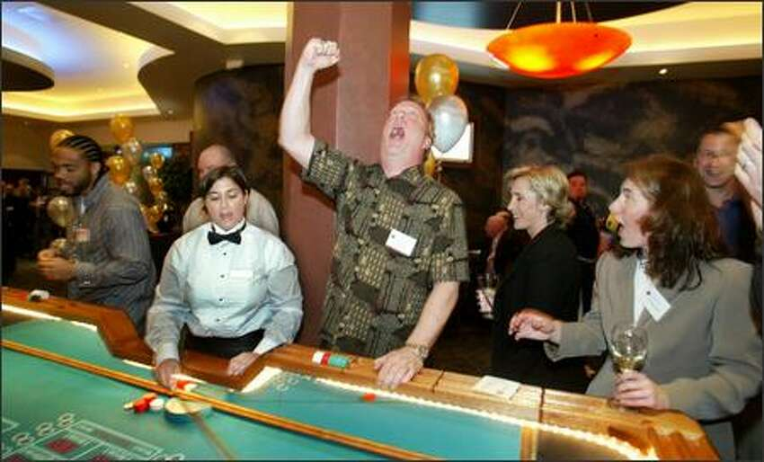KJR Sports Radio talk show host Dave Grosby lets out a roar at the craps table as FSN's Angie Mentink, to Grosby's left, smiles at his antics.