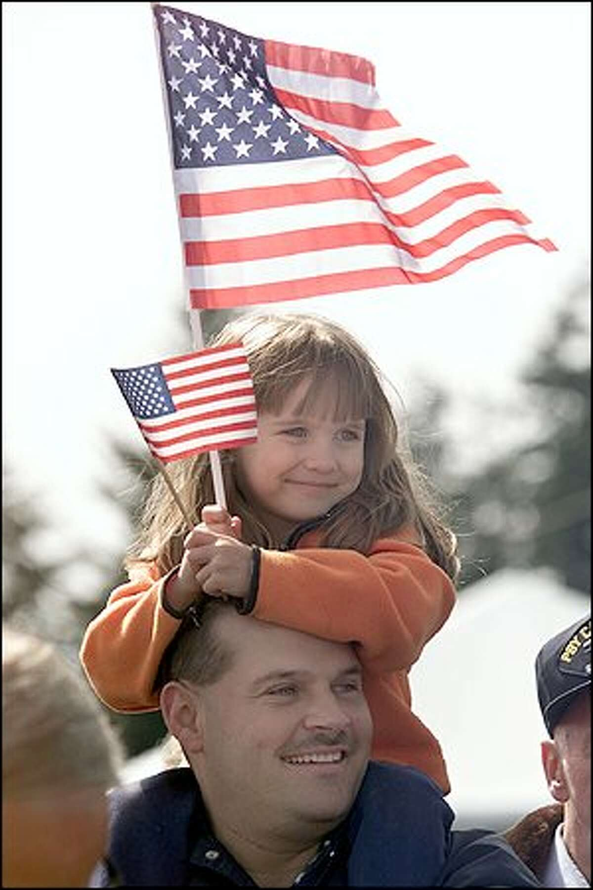 Jamie Bigham, 5, sits on her dad Kevin's shoulders as they wait for VQ-1 to return to Whidbey Island. About 7,000 spectators came to support the crew and give them a heroes' welcome.