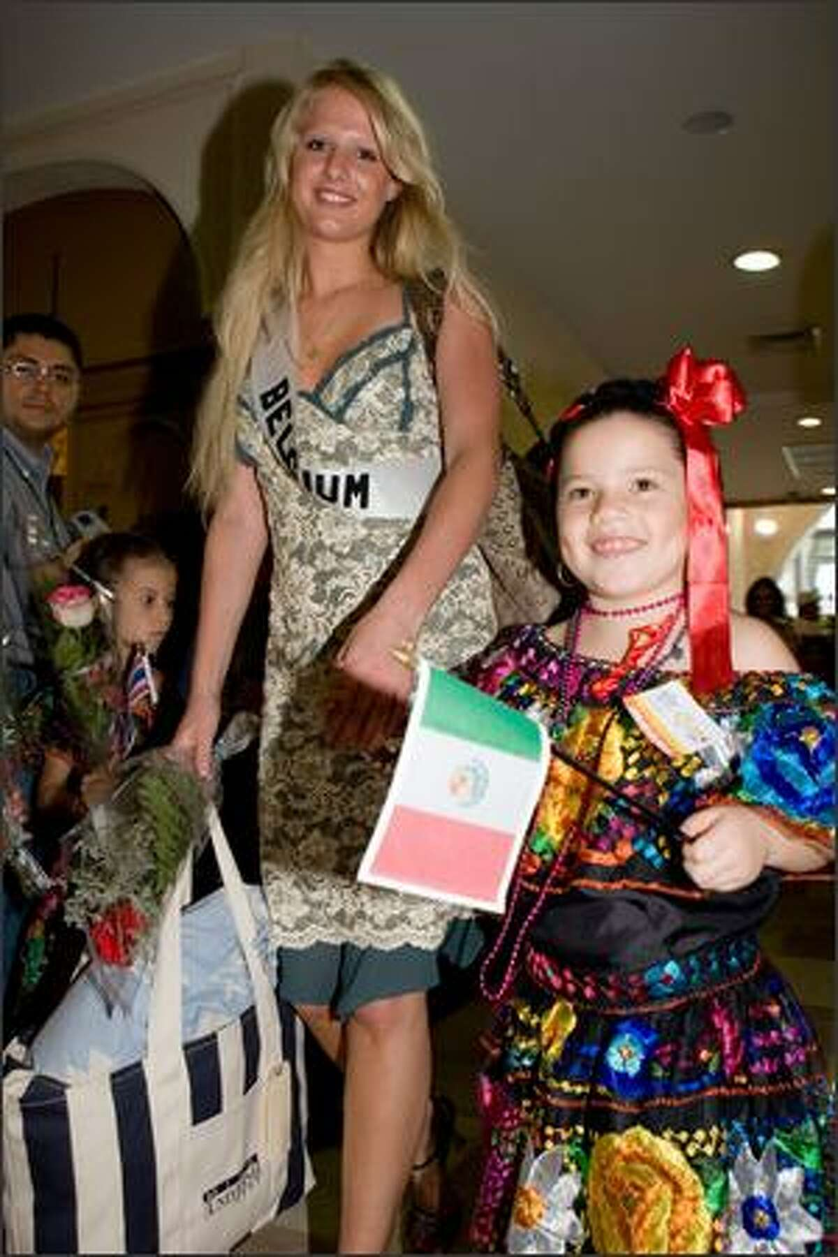 Annelien Coorevits, Miss Belgium 2007, is escorted by a child in traditional Mexican attire to the press conference and photo opportunity at the Crowne Plaza Tuxtla Gutierrez.