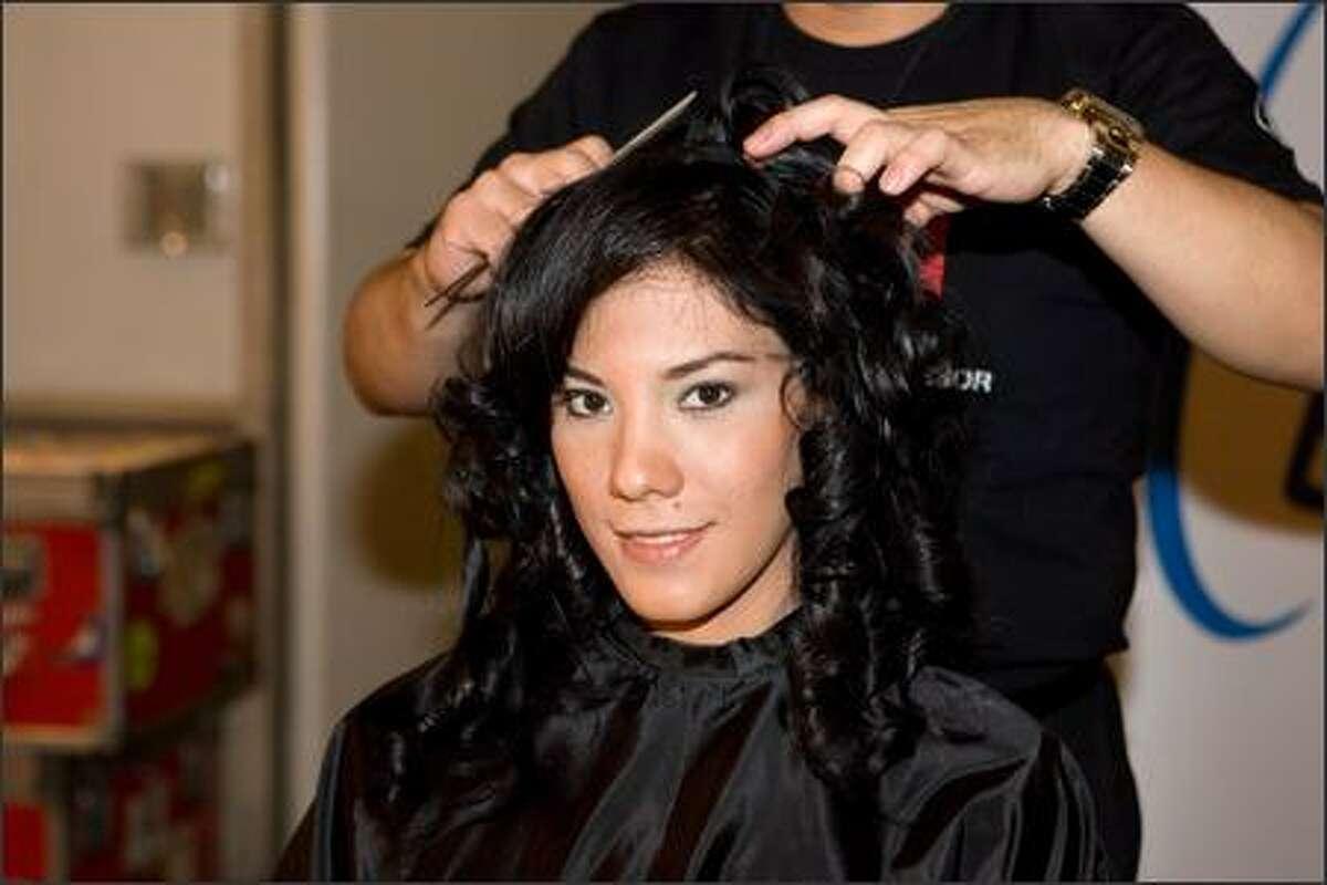 Viktoria Azovskaja, Miss El Salvador, sits as Farouk Systems hairstylists style her hair.