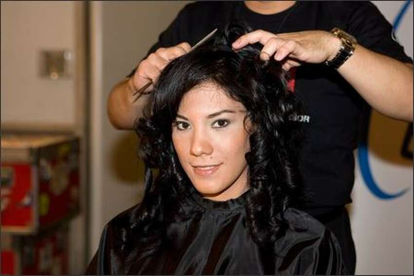 Viktoria Azovskaja, Miss El Salvador, sits as Farouk Systems hairstylists style her hair.