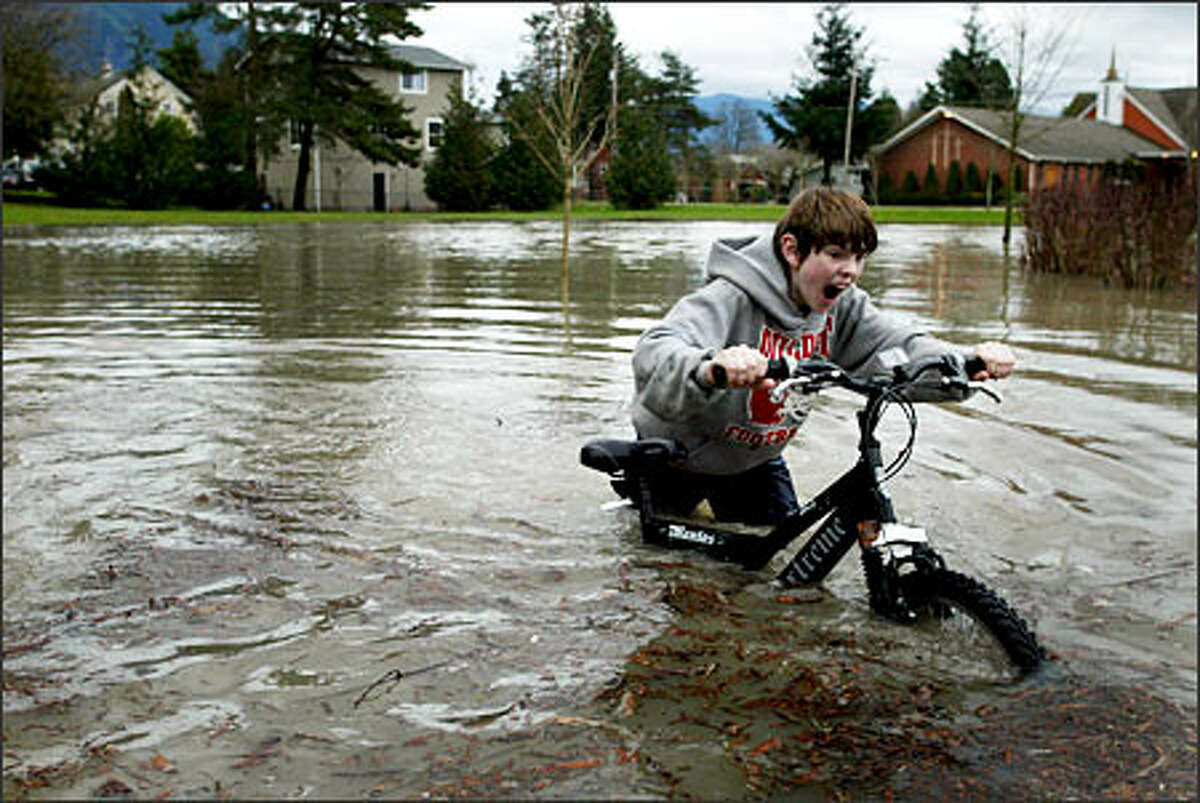 Chris Conley, 12, pushes his bike through a flooded portion of River View Park next to the Snoqualmie River in Snoqualmie.Trujillo: I was dispatched to Snoqualmie to cover the record rainfalll. On the way out the door, I grabbed my knee-high rubber boots thinking that would keep me dry as I sloshed through the mud and rising water. As I photographed the kid pushing his bike, I immersed my boots too deep and water poured over the rim and filled the boots. Next time I have to cover a flood I will take waders.