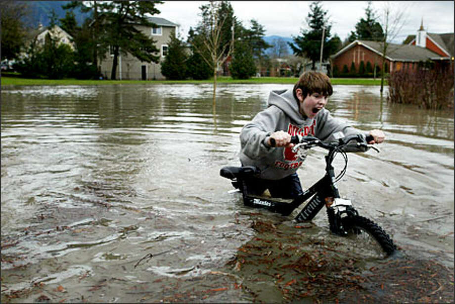 Chris Conley, 12, pushes his bike through a flooded portion of River View Park next to the Snoqualmie River in Snoqualmie.Trujillo:I was dispatched to Snoqualmie to cover the record rainfalll. On the way out the door, I grabbed my knee-high rubber boots thinking that would keep me dry as I sloshed through the mud and rising water. As I photographed the kid pushing his bike, I immersed my boots too deep and water poured over the rim and filled the boots. Next time I have to cover a flood I will take waders. Photo: Joshua Trujillo, Seattlepi.com