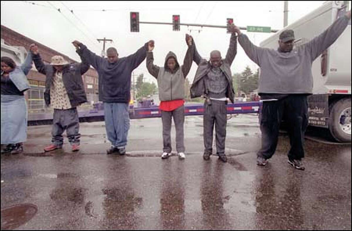 Holding hands, protesters form a circle at the intersection of 23rd Avenue East and East Union Street, during a demonstration yesterday sparked by the shooting death of Aaron Roberts. Protesters stopped traffic for several hours.