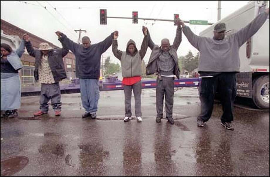 Holding hands, protesters form a circle at the intersection of 23rd Avenue East and East Union Street, during a demonstration yesterday sparked by the shooting death of Aaron Roberts. Protesters stopped traffic for several hours. Photo: Gilbert W. Arias, Seattle Post-Intelligencer