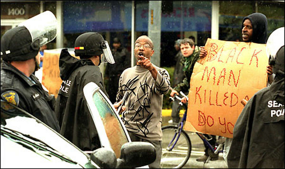 A man confronts Seattle police on 23rd Avenue East and East Union Street Friday during a protest following the shooting death of Aaron Roberts late Thursday night.