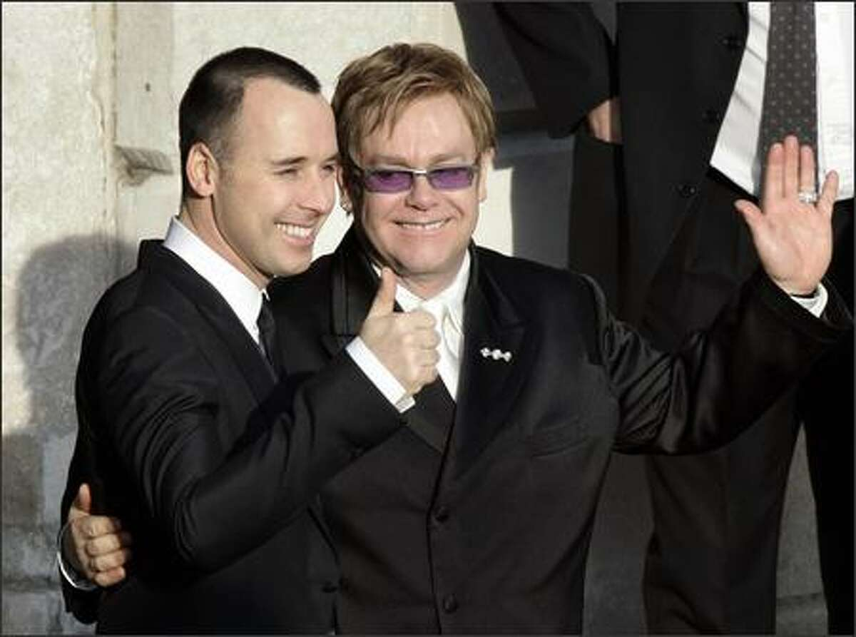Pop star Elton John, right, and his longtime partner David Furnish, embrace as they wave to members of the media and the public after they had a civil ceremony at the Guldhall in the town of Windsor, England. (AP Photo/Lefteris Pitarakis)
