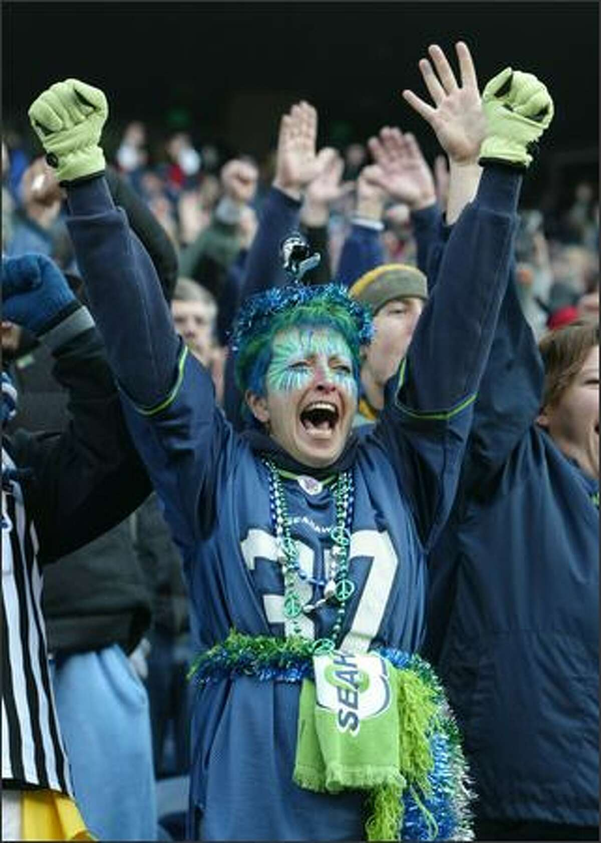Margy Wick, who came all the way from Soap Lake in Eastern Washington to cheer for the Seahawks in Sunday's game against the San Francisco 49ers at Qwest Field, signals touchdown after a Seattle score in the first quarter.