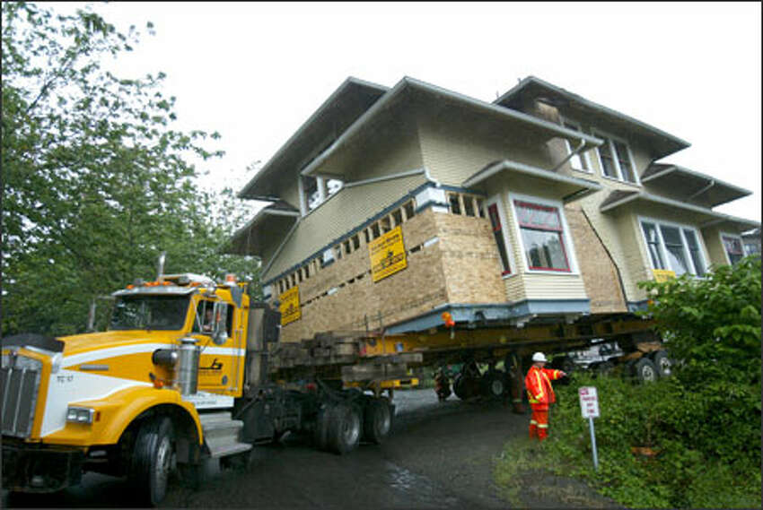 The last residential house on Seattle's Eastlake Avenue East negotiates a tricky turn Sunday on its way to a barge bound for the San Juan Islands, where new owners plan to preserve the 1908 house.