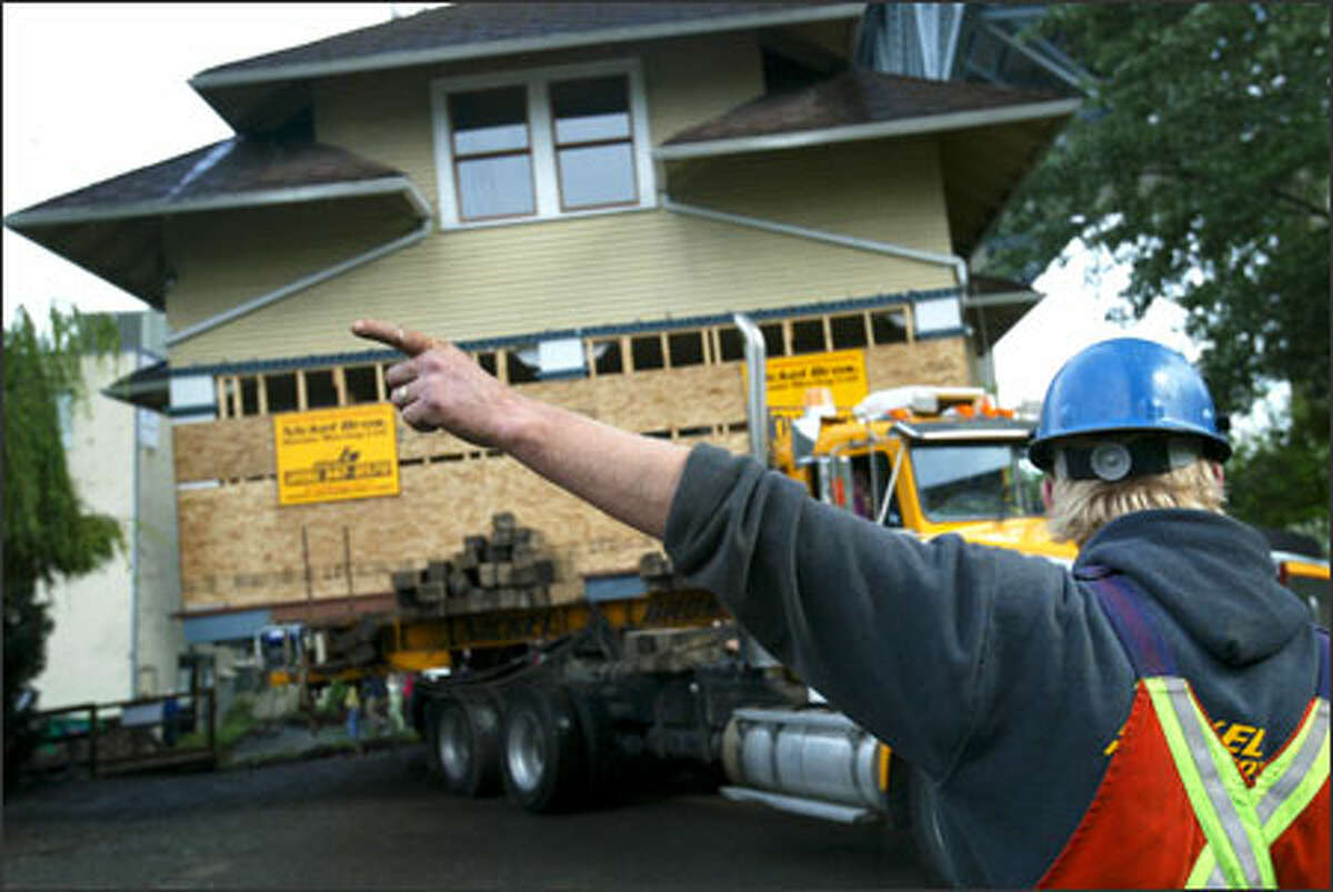 Jeremy Nickel directs a driver as the home begins its journey to a barge waiting on the water.