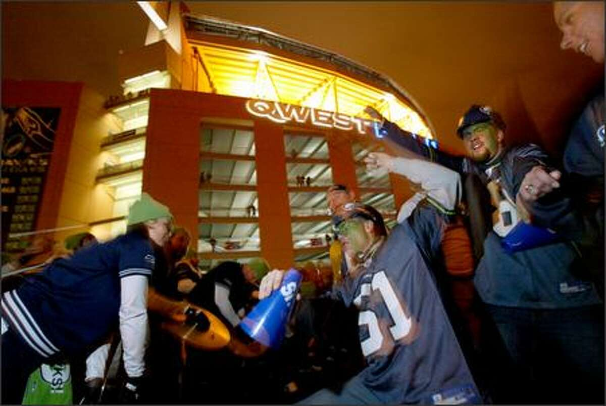 Jim Lussier of Everett, center, dances with members of Blue Thunder outside Qwest Field after the game.