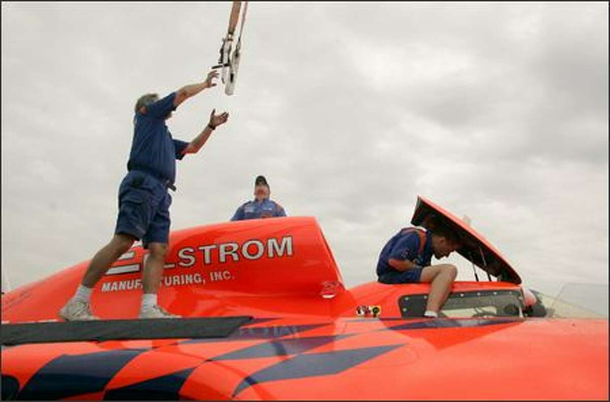 Crew members Dave Heye (from left), Adam Bratvold, and Rick Swanson work on the 1 Miss E-Lam Plus, an unlimited hydroplane based in Ballard, during testing at Stan Sayres pits on Lake Washington Thursday.