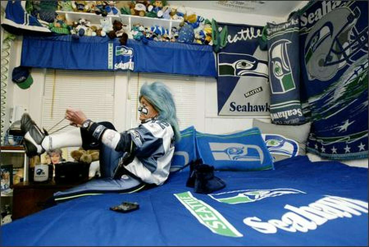 In the bedroom of her Auburn home, Mrs. Seahawk DeDe Schumaier laces up her shoes before heading out for Seattle's game against the St. Louis Rams on Sunday, Nov. 13.
