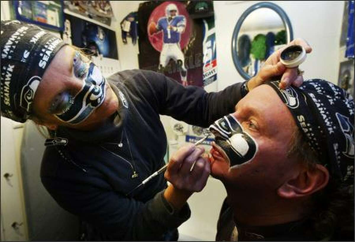 After painting her own face, DeDe Schumaier paints her huband Jeff's face.