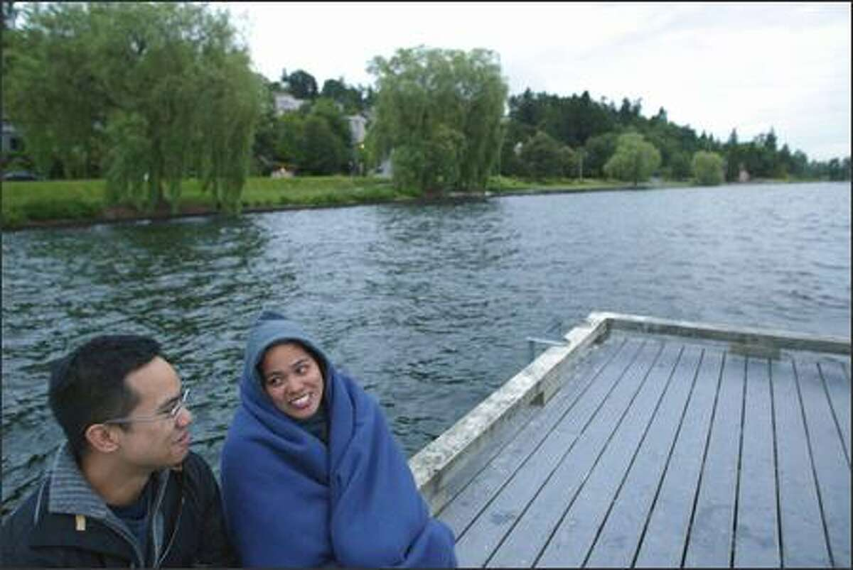 5:17 a.m. -- Cousins Wes DeVera (left) and Catherine Domaoan, both from Seattle, watch for the sun to rise over Lake Washington from Madrona on Wednesday.