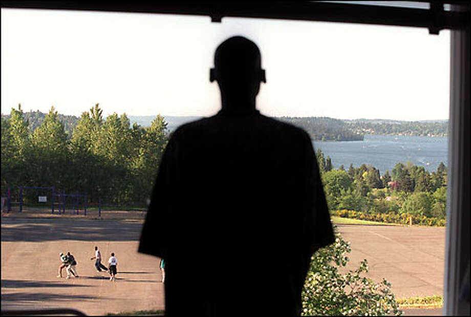 "After arriving in the United States just 10 days before, Tong Tong Mel, 20, gazes over the south end of Lake Washington through a window at the Payam House, a former St. Paul parish convent, in Skyway. ""Payam"" is a Dinka word meaning ""safe harbor."" Outside, fellow refugees from Sudan play a friendly game of basketball. Photo: Grant M. Haller, Seattle Post-Intelligencer"