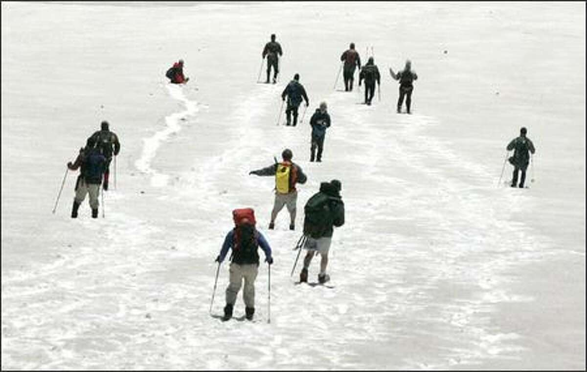 Members of the media descend from the rim of Mount St. Helens across a snow field on Thursday. The climb will soon be open to the public after having been closed since 2004 due to volcanic activity.