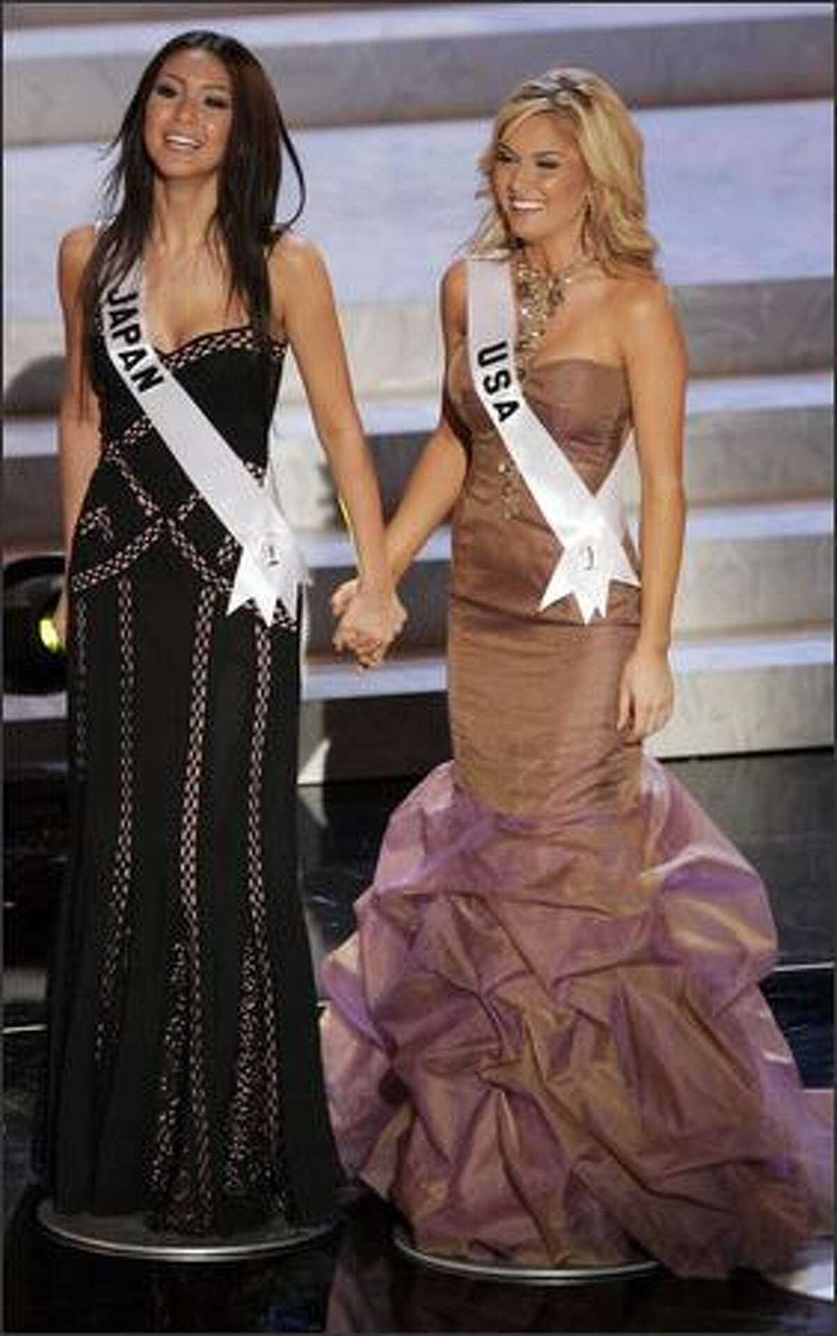 Finalists Kurara Chibana, Miss Japan, left, holds hands with Tara Conner, Miss USA, during the Miss Universe 2006 pageant.