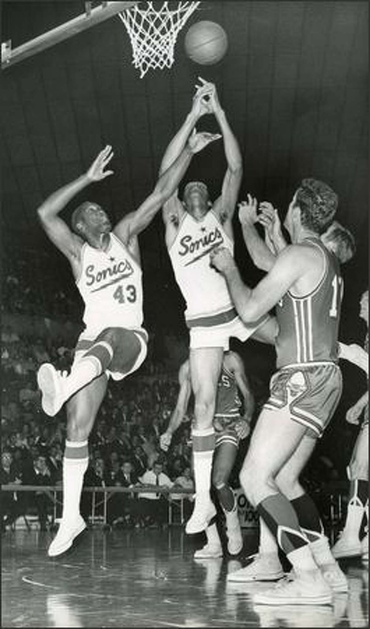 1967: Seattle Supersonics players Plummer Lott and Bob Rule go for a rebound against Chicago.